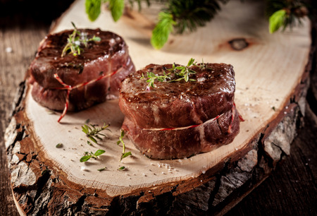 boar: Close Up of Two Roasted Venison Steak Filets Seasoned with Fresh Herbs and Served on Rustic Wood Plank