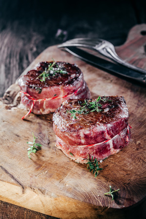 corded: Close Up of Two Rare Venison Steak Filets Seasoned with Fresh Herbs on Wooden Cutting Board with Cutlery Stock Photo