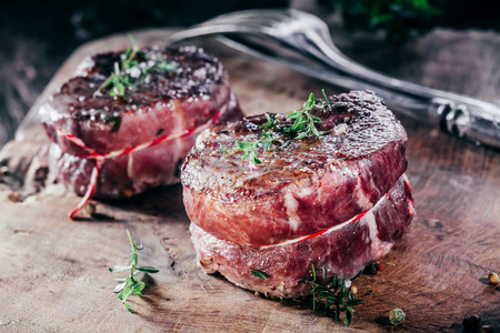 corded: Close Up of Two Rare Beef Steak Filets Seasoned with Fresh Herbs on Wooden Cutting Board with Cutlery Stock Photo
