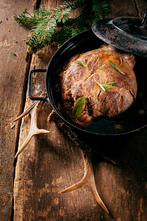 roasting pan: High Angle View of Cooked Venison Roast in Roasting Pan Seasoned with Fresh Herbs on Wooden Surface with Evergreen Branches and Deer Antler