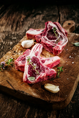 lamb chop: Close Up of Raw Lamb Filets Seasoned with Garlic, Salt and Fresh Herbs on Rustic Wooden Board