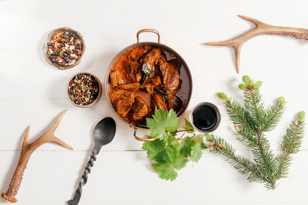 Copper, pot of spicy deer goulash surrounded by spice rub, red wine and peppercorns for a marinade with pair of shed antlers in the corners, overhead view Imagens