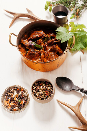 Goulash: Delicious spicy venison goulash with diced deer meat in a copper pot with spice rub and red wine used in the marinade, high angle on white