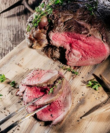 red cooked: High Angle View of Sliced Rare Venison Roast Seasoned with Fresh Herbs and Served on Wooden Cutting Board with Deer Antlers