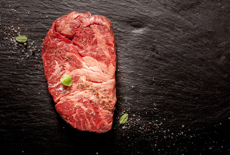 High Angle View of Raw Chuck Eye Beef Steak Seasoned with Herbs and Spices on Dark Grey Textured Surface with Copy Space