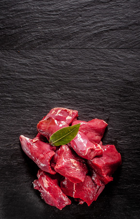 Cervine wild deer venison trimmed and diced standing ready for cooking in a tasty venison goulash on a textured black background with copyspace, overhead view Stock Photo