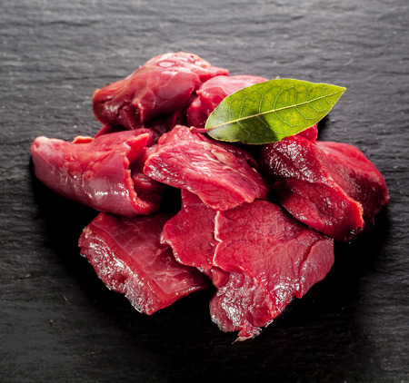 steak: Uncooked lean healthy diced deer steak for a venison goulash with a bay leaf on a textured dark background, close up high angle