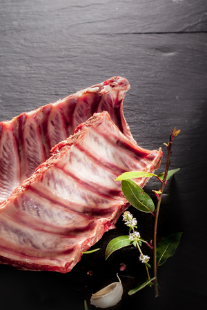 High Angle View of Raw Split Spare Ribs with Fresh Herbs on Textured Grey Surface with Copy Space photo