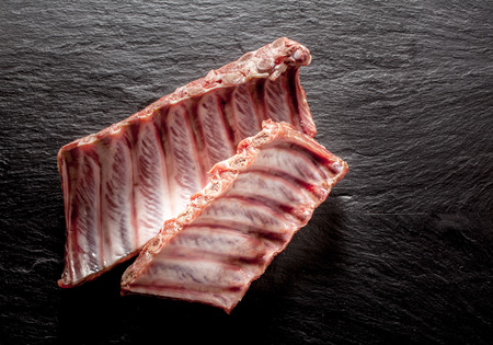 spare ribs: High Angle View of Raw Split Spare Ribs on Textured Grey Surface with Copy Space