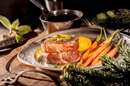 vegetable tin: Close Up of Boar Filet Steak Served on Metal Plate with Carrots on Wooden Tray with Evergreen Sprigs