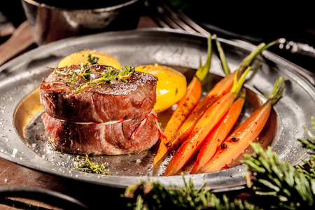 Close Up of Boar Steak Served on Metal Plate with Carrots on Wooden Tray with Evergreen Sprigs Stock Photo
