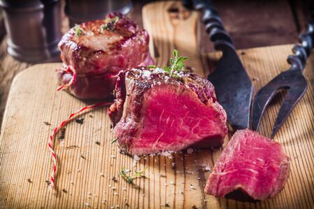 Rare Boar Filets Seasoned with Fresh Herbs on Wooden Cutting Board with Metal Serving Utensils 스톡 콘텐츠