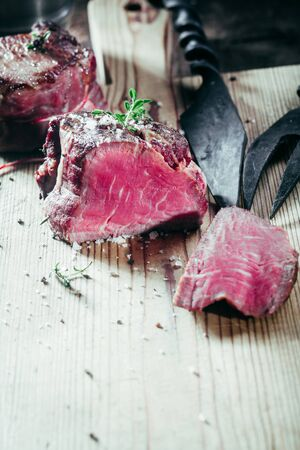 filets: Rare Filets Seasoned with Fresh Herbs on Wooden Cutting Board with Metal Serving Utensils Stock Photo