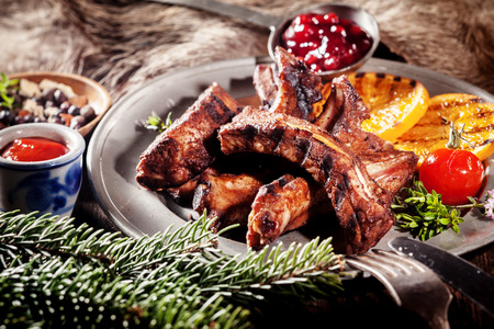 Appetizing BBQ Boar Spare Ribs with Grill Marks Served on Platter with Grilled Fruit and Sauces Banco de Imagens - 40504480