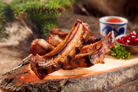 Appetizing BBQ Boar Spare Ribs with Grill Marks Served on Rustic Wood Plank Accompanied by Sauces