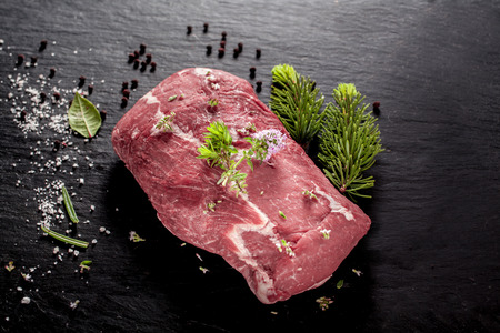 wild: Slab of uncooked wild boar steak for roasting on a barbecue seasoned with spices and herbs lying alongside a small fir branch on a dark background, overhead view