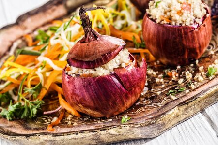 couscous: Close Up of Healthy Vegetarian Couscous Stuffed Red Onions on Decorative Platter with Fresh Salad Stock Photo