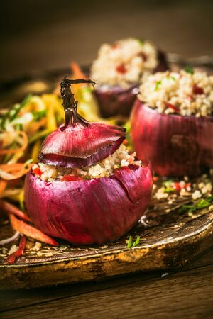 Healthy Vegetarian Couscous Stuffed Red Onions Served on Decorative Platter with Salad