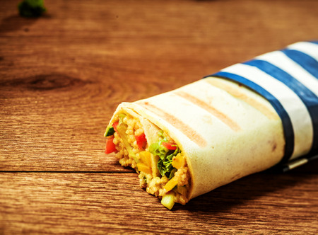 Close Up of Healthy Vegetarian Couscous Filled Grilled Burrito Wrap with Blue and White Striped Wrapper on Wooden Surface