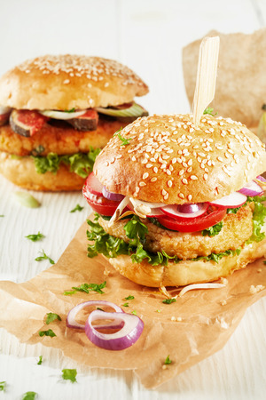 couscous: Two Vegetarian Couscous Burgers with Fresh Toppings and Herbs on Sesame Seed Rolls with Onion Slices on Brown Paper Wrapper