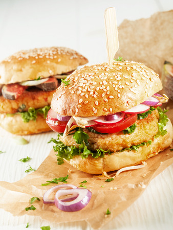 vegetarians: Two Vegetarian Couscous Burgers with Fresh Toppings and Herbs on Sesame Seed Rolls with Onion Slices on Brown Paper Wrapper