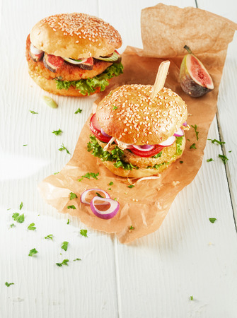 couscous: High Angle View of Two Vegetarian Couscous Burgers with Fresh Toppings and Herbs on Sesame Seed Rolls with Onion Slices on Brown Paper Wrapper with Copy Space