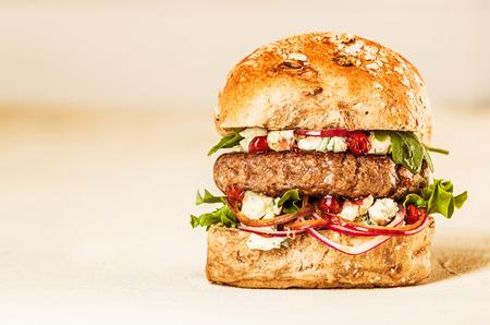 hamburguesa: Perfil de Soltero apetitosa y jugosa hamburguesa repletas de frescos Ingredientes en Pan de Trigo saludable en Studio con fondo liso y espacio de la copia
