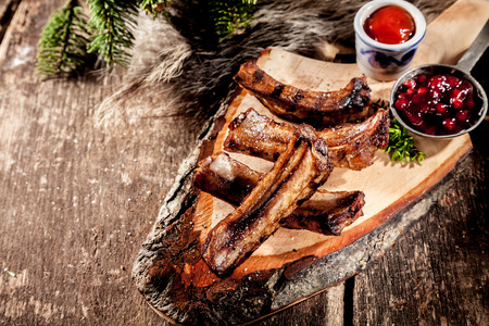 High Angle View of Appetizing BBQ Spare Ribs with Grill Marks Served on Rustic Wood Plank Accompanied by Sauces with Copy Space photo