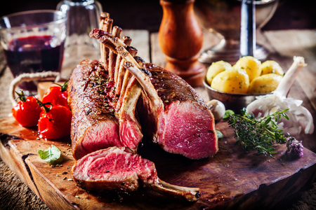 Rare Rectangle Rack of Lamb on Wooden Cutting Board Surrounded by Fresh Herbs and Ingredients