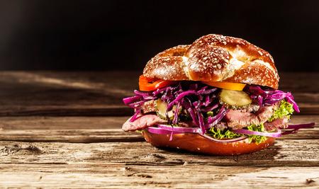 hamburguesa: Hamburguesa deliciosa con rodajas de carne asada rara y frescos ingredientes de la ensalada en un rollo crujiente recién horneado con semillas de pie sobre una mesa de madera rústica con copyspace