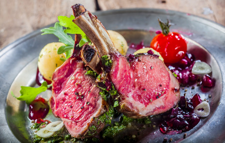 pewter: Rare cooked lamb cutlets from a rectangle or rack of lamb served on a bed of fresh salad with baby potatoes on a rustic pewter plate