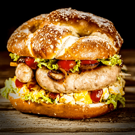 german sausage: Delicious crusty burger with smoked German sausage, fresh salad ingredients and tomato ketchup, close up square view