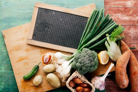 bounty: Vista elevada del Bounty de verduras frescas en la tabla de cortar de madera con Junta Negro Marcado con Retícula, Naturaleza muerta en el fondo de madera rústica Foto de archivo