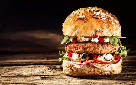 delicious: Close Up of Burger Piled High with Fresh Toppings on Whole Grain Artisan Bun, on Rustic Wooden Surface with Dark Background and Copy Space