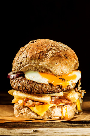 Wholesome egg and bacon burger with a beef patty, fried egg and bacon, cheese, onion and french fries on a wholegrain roll served as a rustic takeaway on brown paper photo