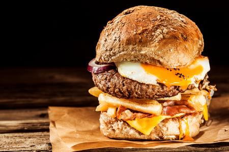 Tasty egg and bacon cheeseburger with a ground beef patty, fried egg, cheese, french fries, onion and bacon served on a fresh roll on brown paper with copyspace photo