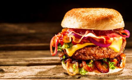 hamburguesa: Hamburguesa con queso delicioso con ingredientes de la ensalada en una hamburguesa de ternera a la parrilla servido sobre un crujiente bollo de pan de oro sobre una mesa de madera rústica con copyspace