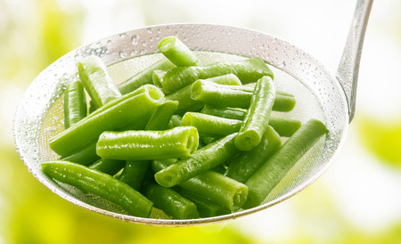 accompaniment: Freshly harvested diced steamed or boiled green runner beans in a kitchen ladle to be served as an accompaniment to a meal