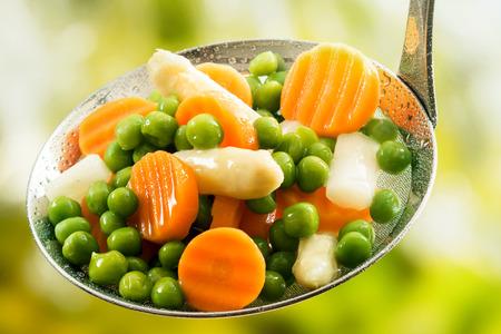 Assortito al vapore o bollita appena raccolte giovani verdure con piselli, carote e asparagi in una cucina rustica siviera Archivio Fotografico