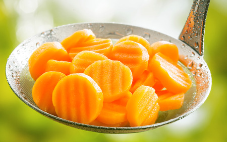 zanahoria: Saludable corte arruga hervido o al vapor de granja en rodajas las zanahorias frescas en una cuchara de cocina listo para ser servido como acompañamiento de una comida