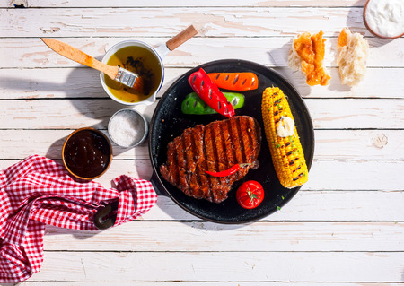 Marinated spicy grilled rib eye beef steak served on a metal skillet with barbecued peppers and corn on the cob on an outdoor white wooden table, overhead view