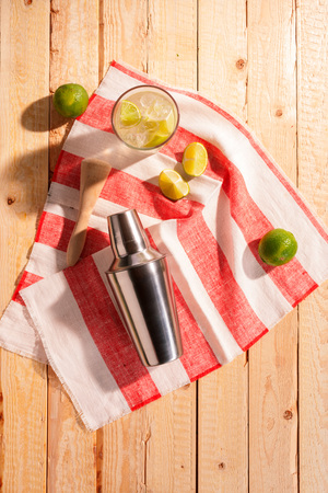 martini shaker: Cocktail shaker with an iced martini cocktail and fresh lemon and lime on a striped red and white napkin on a rustic wooden table outdoors in sunshine