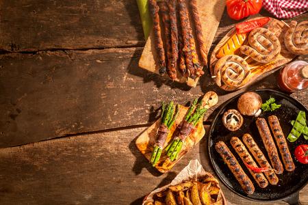 Diverse gegrilde gerechten, waaronder worstjes, aardappelpartjes en asperges spek wraps van een zomerse barbecue op een rustieke houten picknicktafel met copyspace Stockfoto