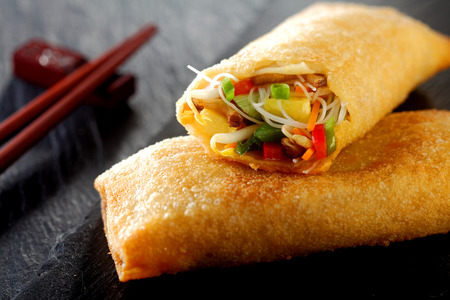 Crispy fried spring roll with filled with fresh vegetables and sprouts for delicious Chinese cuisine on a wooden table with chopsticks