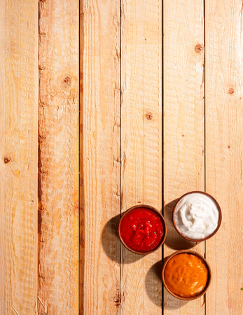 mayonnaise: Individuals sauces for a summer barbecue standing ready on a wooden picnic table outdoors with tomato ketchup, mayonnaise and spicy mustard, overhead view