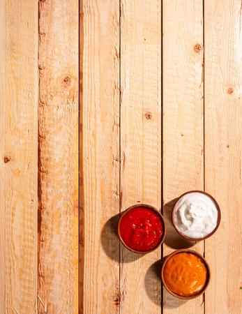mahonesa: Los individuos salsas para una barbacoa de verano de pie listo en una mesa de picnic de madera al aire libre con salsa de tomate, mayonesa y mostaza picante, vista aérea