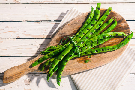 top down: Bunch of grilled green runner beans cooked over a barbecue served on a wooden board on a white picnic table outdoors in summer, overhead view Stock Photo