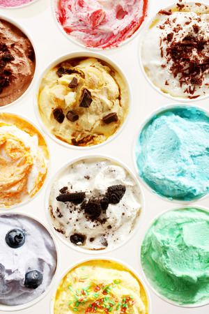 dessert: Overhead view of rows of individual tubs of colorful Italian ice cream on white with assorted colors and flavors for refreshing summer desserts