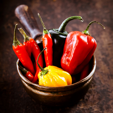 cayenne: Assorted Red hot cayenne chili peppers,habanero colorful yellow and red sweet pepper displayed ready for cooking in a rustic bowl on a wooden counter