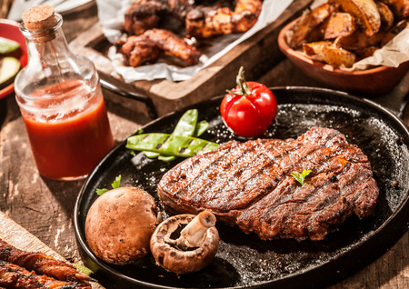 Rustic country meal of grilled ribe eye beef steak with mushrooms and tomato served with homemade ketchup and assorted barbecued meats on a summer picnic Stock Photo